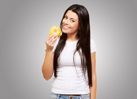 portrait of young woman eating a donut over grey Stock Photo - 13280173