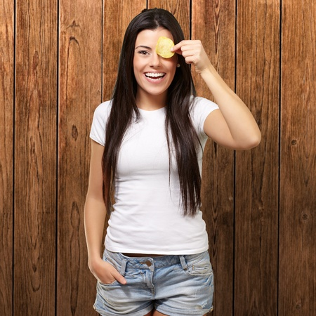portrait of young woman holding a potato chip in front of her eye against a wooden wall Stock Photo - 13280131