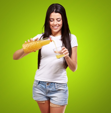portrait of young woman pouring orange juice on glass over green photo