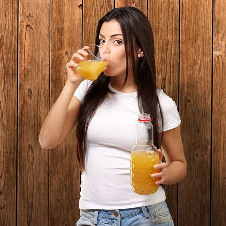 portrait of young girl drinking orange juice against a wooden wall photo