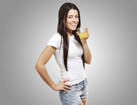 woman holding a glass of orange juice against a grey background photo