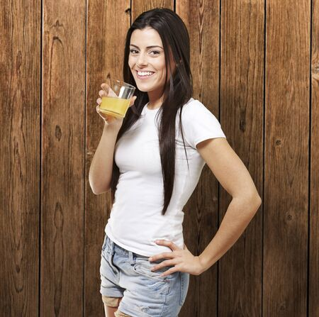 woman holding a glass of orange juice against a wooden background photo