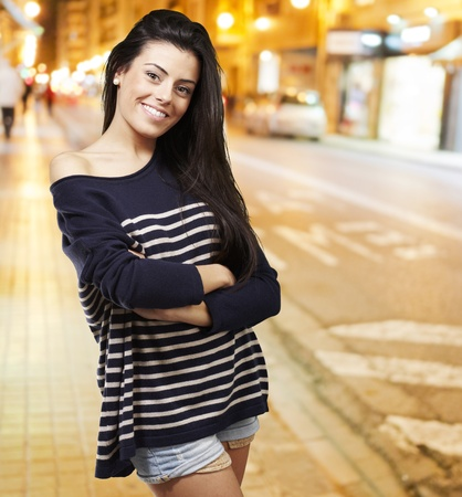portrait of a pretty young woman smiling against a city night background photo