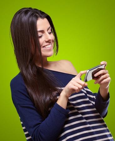 Portret van een jonge vrouw aan te raken een moderne mobiele over groene Stockfoto