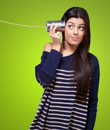Portrait de jeune femme entendre à travers une boîte de conserve sur fond vert