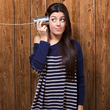 tin can telephone: portrait of young woman hearing through a tin can against a wooden wall Stock Photo