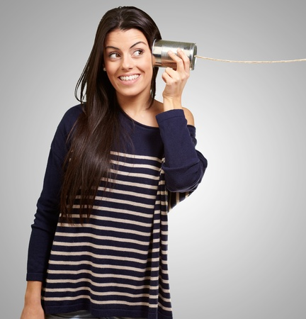 tin can telephone: Young woman hearing using a metal tin can over grey background Stock Photo