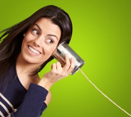 Jonge vrouw gehoor behulp van een metalen blik over groene achtergrond Stockfoto