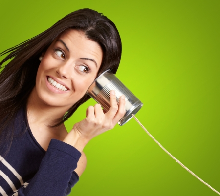 tin can phone: Young woman hearing using a metal tin can over green background