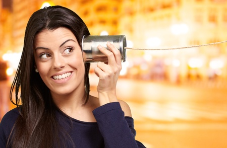 tin can telephone: Young woman hearing using a metal tin can at night city