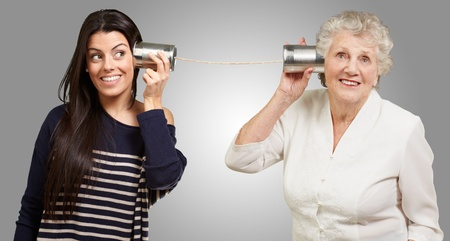 tin can phone: portrait of young girl and her grandmother hearing sounds using a metal tin can