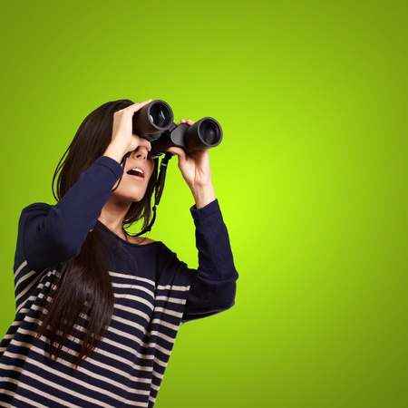 portrait of young girl looking through a binoculars over green Stock Photo - 13280222