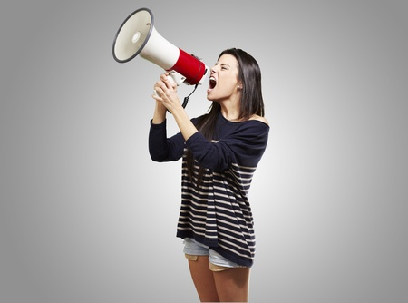 young woman shouting with a megaphone against a grey background photo