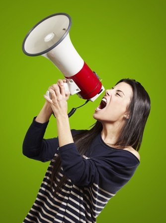 young woman shouting with a megaphone against a green background photo