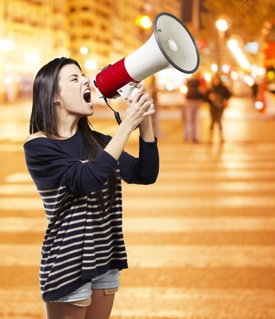 young woman shouting with a megaphone against a city night background photo