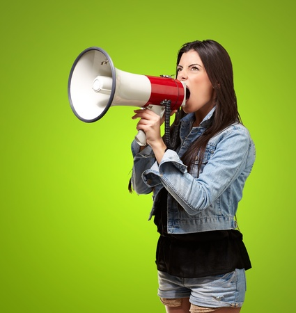 portrait of young woman screaming with megaphone against a green background photo