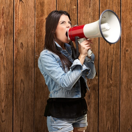 portrait of young woman screaming with megaphone against a wooden wall Stock Photo - 13280258