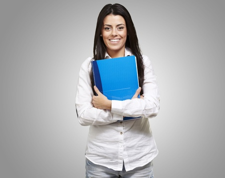 young woman smiling and holding a notebook against a grey background Stock Photo - 13280311