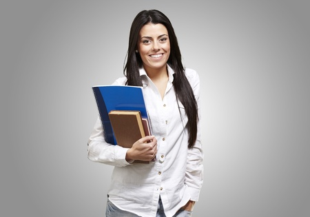 young student holding books and smiling against a grey background Stock Photo - 13280269