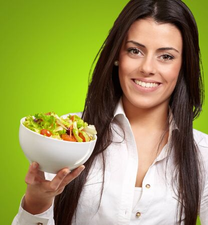 portrait of young woman holding salad over green photo