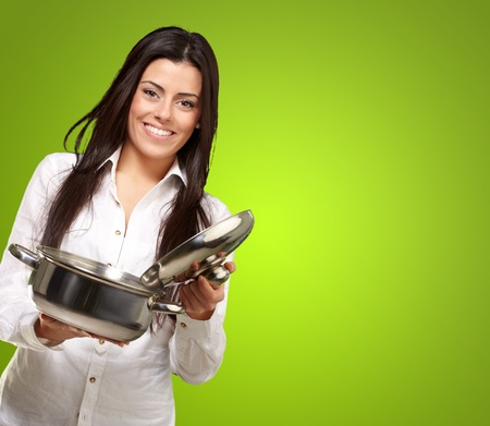 portrait of young girl opening sauce pan over green background photo