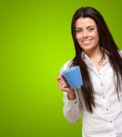 women holding cup: young girl holding cup over green background