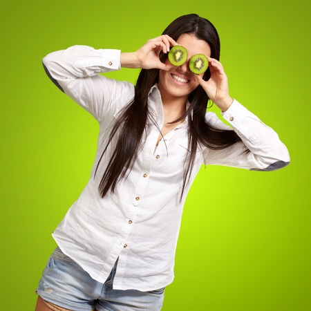 portrait of young girl holding kiwi slices in front of her eyes over green photo
