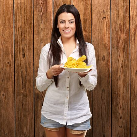 portrait of young woman holding a potato chips plate against a wooden wall Stock Photo - 13280203