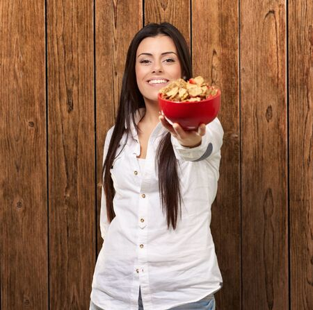 portrait of young woman offering cereals bowl against a wooden wall photo