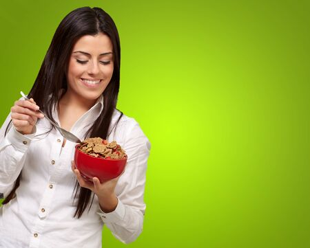 portrait of healthy young woman eating cereals over green photo