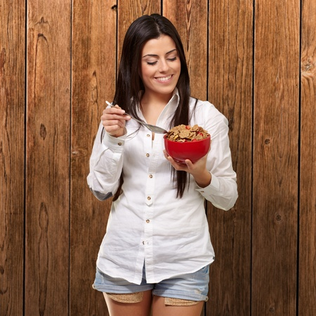 portrait of healthy young woman eating cereals against a wooden wall photo