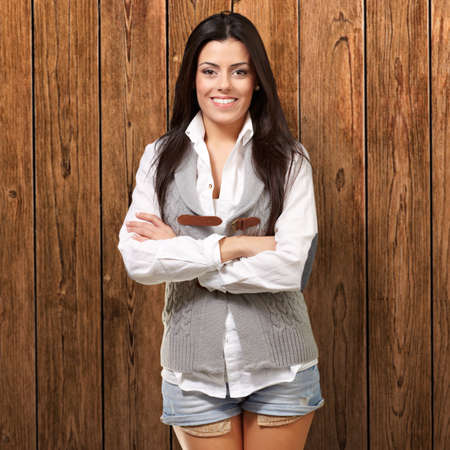 portrait of a happy girl smiling against a wooden wall photo