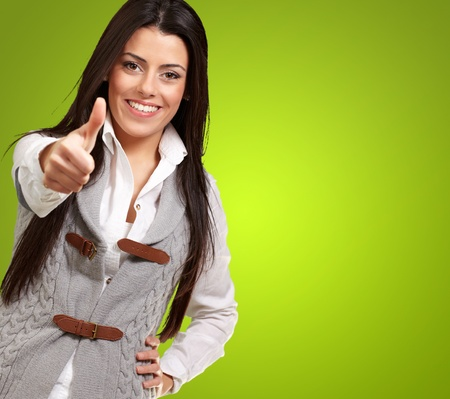 portrait of a pretty young girl doing good gesture over green background photo
