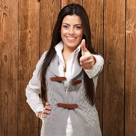 portrait of a pretty young girl doing good gesture against a wooden wall Stock Photo - 13280178