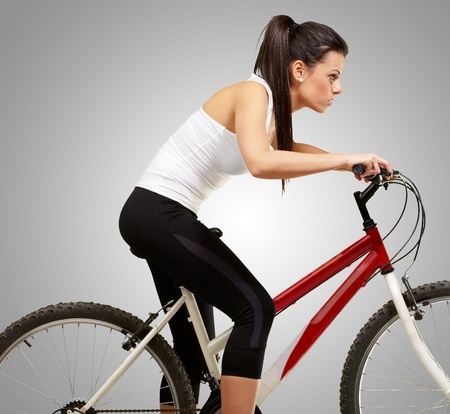 young sporty girl cycling over grey background photo
