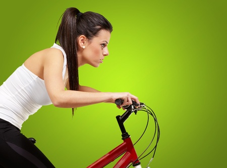 young sporty girl cycling over green background photo