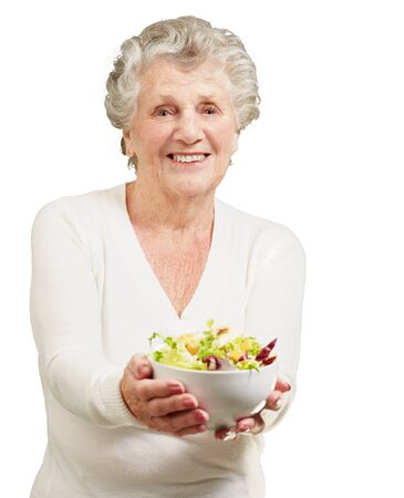 old people eating: portrait of senior woman showing a fresh salad over white background