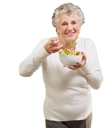 over eating: portrait of senior woman eating a fresh salad over white background Stock Photo