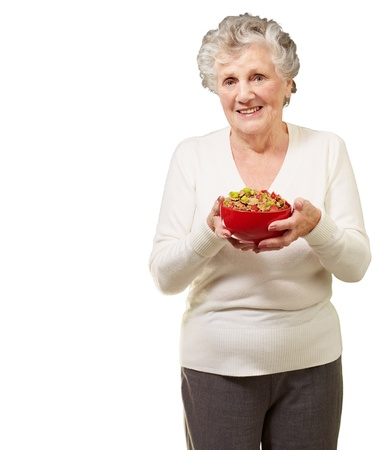 portrait of healthy senior woman holding cereals bowl over white background photo