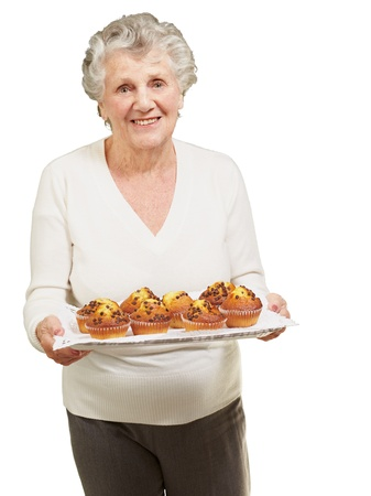 portrait of senior woman showing homemade muffins over white photo