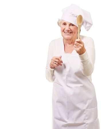 portrait of senior cook woman holding a wooden spoon over white background photo