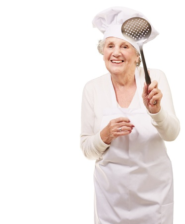 portrait of sweet senior cook woman holding a metal spoon over white photo
