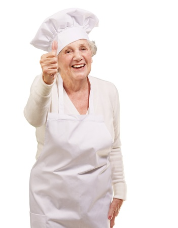 portrait of cook senior woman doing approval gesture over white background photo