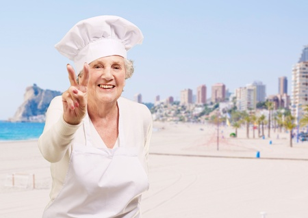 portrait of senior cook woman doing good gesture against a beach photo