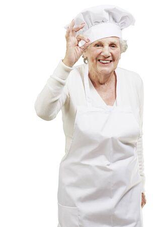 mujeres cocinando: cocinero mujer mayor haciendo un excelente símbolo sobre un fondo blanco