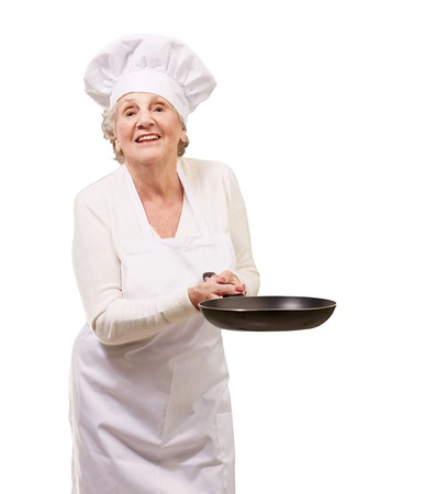 pan asian: portrait of a friendly cook senior woman holding pan over white background