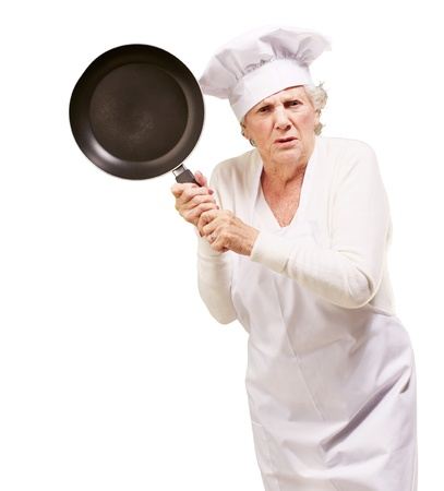 Cook senior woman angry trying to hit with pan over white background photo