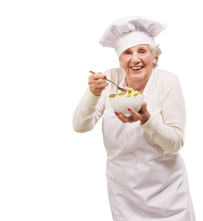 portrait of senior cook woman eating salad over white Stock Photo - 13607640