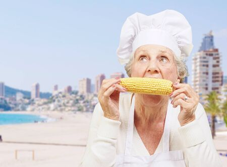 culinary tourism: portrait of senior cook woman eating corn cob against a beach Stock Photo
