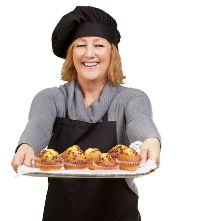 portrait of cook woman showing a homemade muffins tray over white background photo